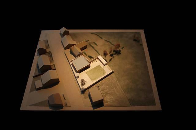 Een maquette van het dorpshuis met een ommuurd dorpspleintje voor evenementen